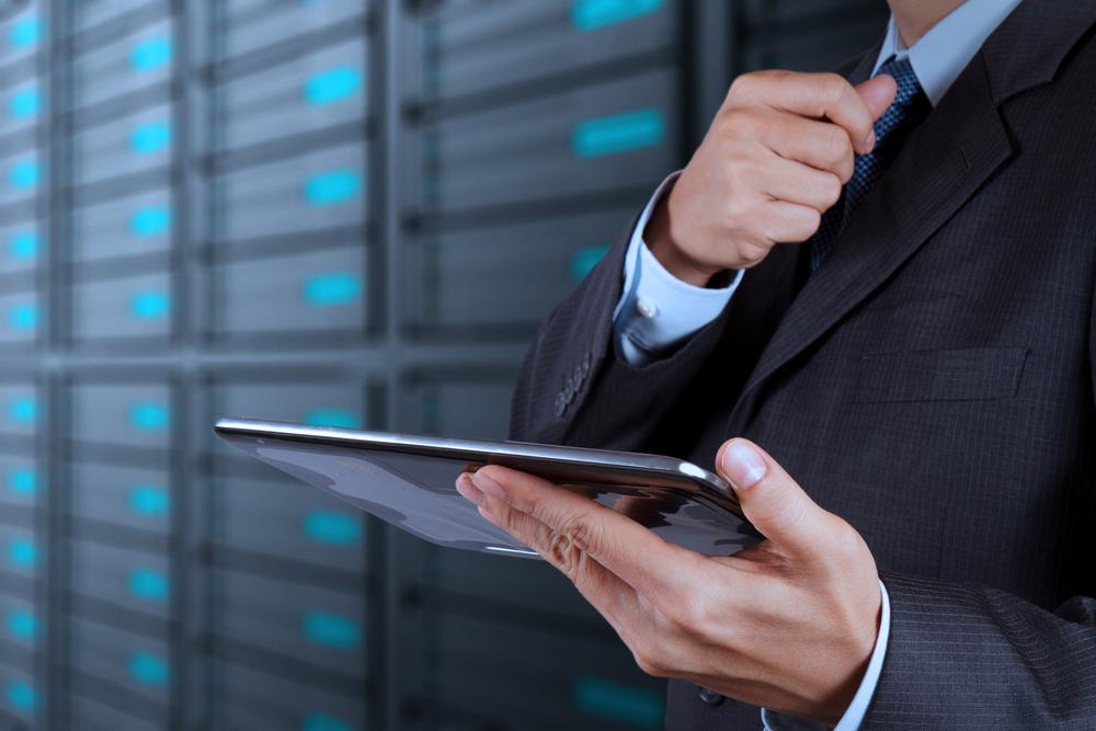 mano di un uomo d'affari che usa il tablet e nello sfondo un data center