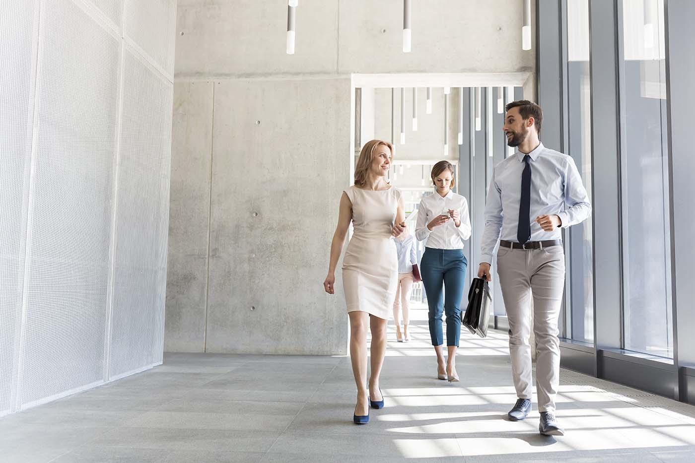 Uomo e donna d'affari che camminano lungo un corridoio